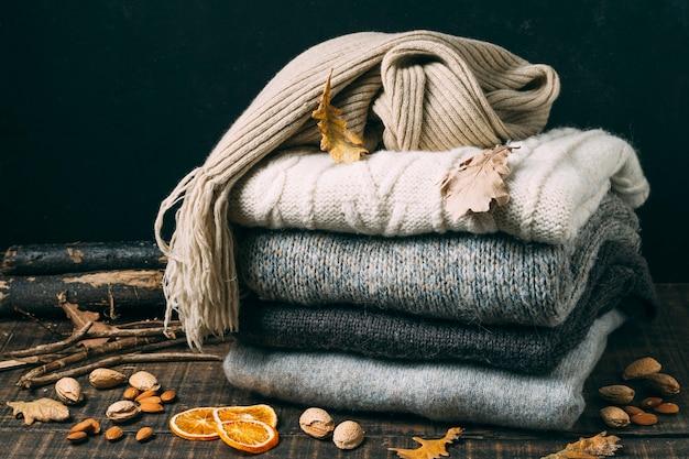 Montón de suéteres de invierno con hojas