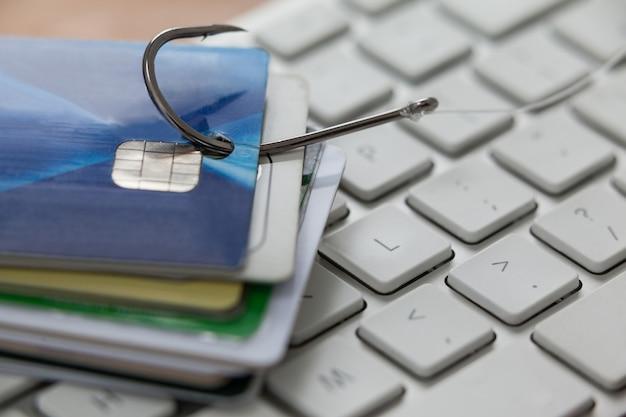 Montón de tarjetas de crédito en el anzuelo de pesca en la computadora portátil