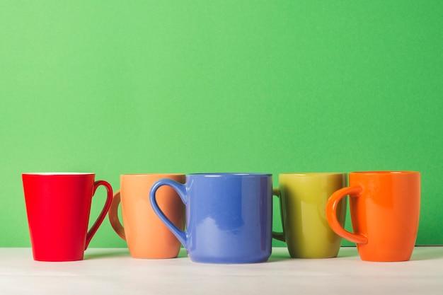 Un montón de tazas multicolores de café o té sobre un fondo verde. el concepto de una compañía amigable, una familia numerosa, reunirse con amigos para una taza de té o café.