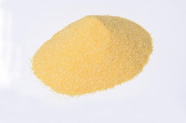 Montón de textura granulada de harina de maíz sobre fondo blanco.