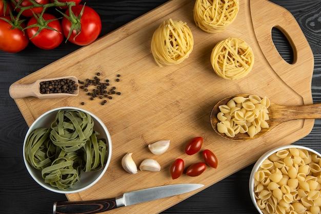 Un montón de tomates con pasta italiana alrededor