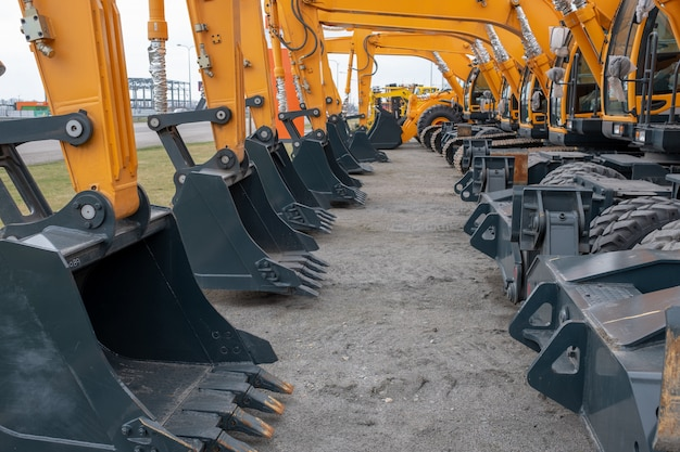 Un montón de tractores amarillos o excavadoras en una exposición
