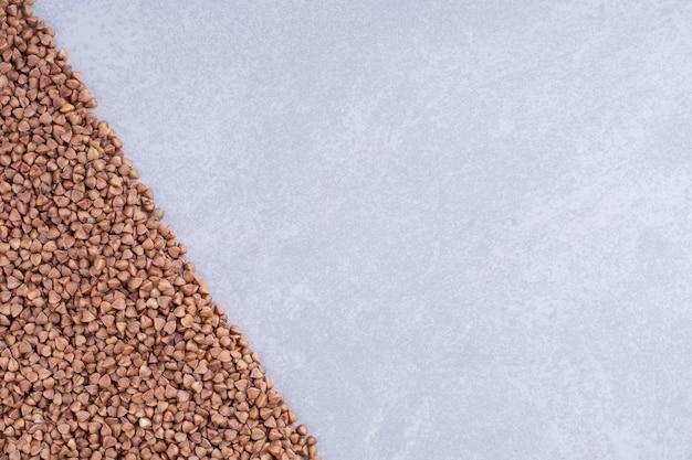 Montón de trigo sarraceno dispuesto en forma triangular sobre la superficie de mármol