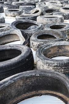 Un montón de viejos neumáticos de automóviles usados de cerca sobre fondo blanco.