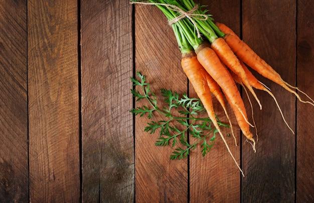 Montón de zanahorias frescas con hojas verdes sobre la mesa de madera
