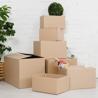 Montones de cajas de cartón contra la pared blanca.
