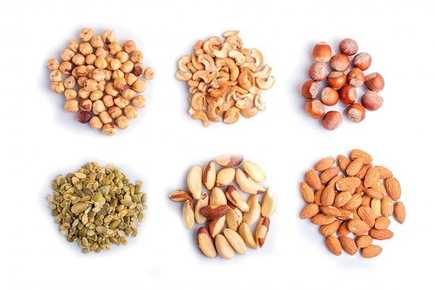Montones de diversos frutos secos y semillas aisladas sobre fondo blanco.