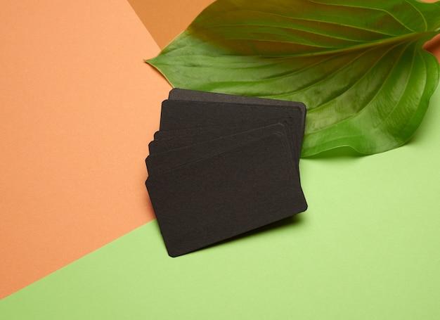 Montones de tarjetas de visita vacías de papel negro sobre fondo naranja-verde