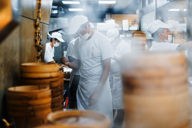 Montones de vapores de bambú apilables están humeando por dim sum frente al restaurante con chefs borrosos en el fondo.