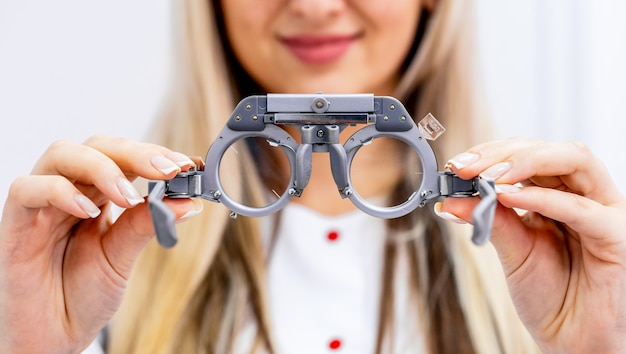 Montura de prueba oftalmológica y anteojos de prueba en manos de mujeres.