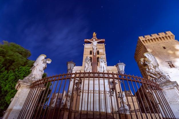 Monumento de la crucifixión de jesús bajo un cielo nocturno en la plaza de la catedral de nuestra señora de las doms en aviñón