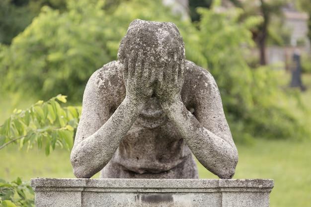 Monumento del hombre con las manos sobre su cabeza en una tumba en un cementerio