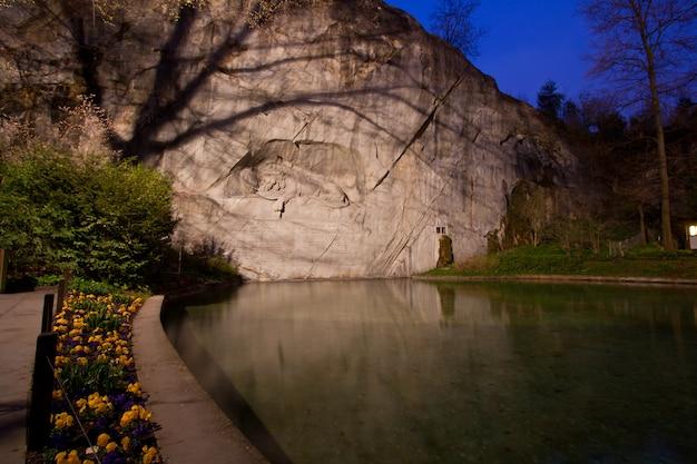 Monumento del león moribundo en lucern suiza crepúsculo con flor
