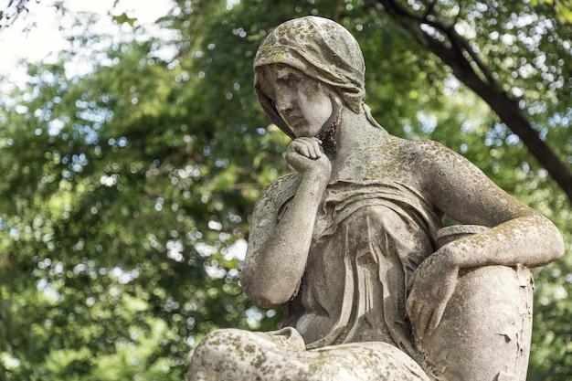 Monumento de mujer joven en una tumba en un cementerio