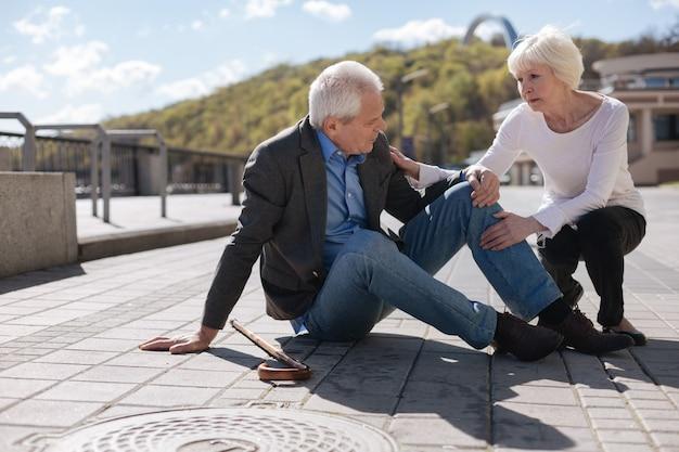 Moody enfermo enfermo que permanece en el suelo sintiendo dolor de rodilla mientras una mujer agradable lo consuela