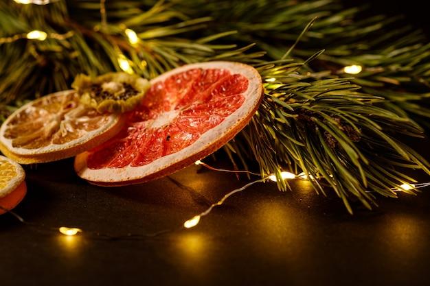 Moody vacaciones creativas navidad año nuevo alimentos frutas con pomelo seco, kiwi, naranja y limón con rama de abeto con cálidas luces led, ángulo de visión, enfoque selectivo