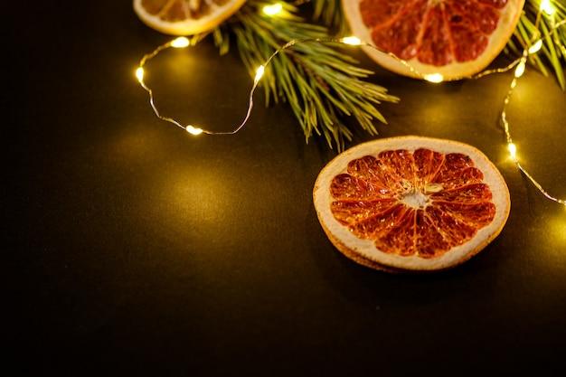 Moody vacaciones creativas navidad año nuevo alimentos frutas con pomelo seco, kiwi, naranja y limón con rama de abeto con cálidas luces led, ángulo de visión, espacio de copia