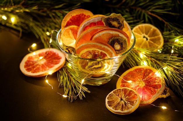 Moody vacaciones creativas navidad año nuevo alimentos frutas con pomelo seco, kiwi, naranja y limón en un recipiente de vidrio con rama de abeto con cálidas luces led, ángulo de visión