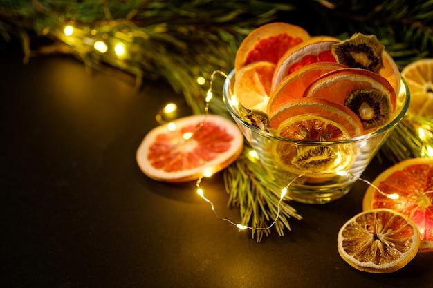 Moody vacaciones creativas navidad año nuevo alimentos frutas con pomelo seco, kiwi, naranja y limón en un tazón de vidrio con rama de abeto con cálidas luces led, ángulo de visión, espacio de copia