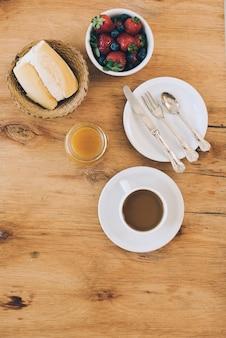 Moras frecas; un pan; taza de mermelada y café sobre fondo con textura de madera