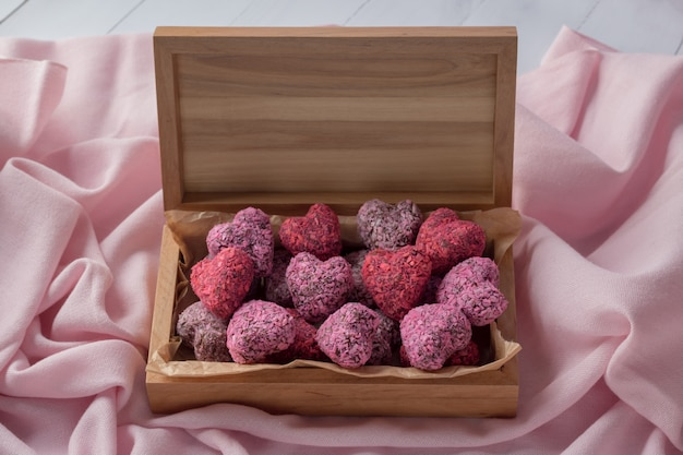 Mordeduras de energía en forma de corazón para el día de san valentín en caja de madera sobre tela rosa, vista superior
