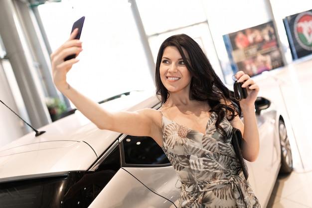 La morena admirable se hace una selfie y se posa cerca de su auto nuevo en el concesionario