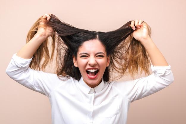 Morena atractiva en camisa blanca tira de sus pelos y grita. mujer volviéndose loca