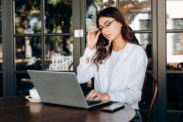 Morena atractiva con gafas trabajando en la computadora portátil en un nuevo proyecto