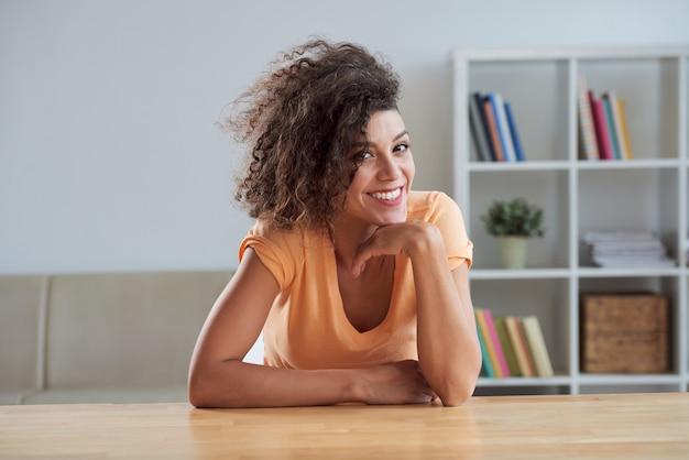 Morena caucásica joven rizada sentada a la mesa en casa y sonriendo a la cámara
