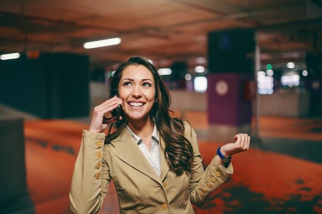 Morena caucásica sonriente vestida elegante usando un teléfono inteligente y mirando hacia el estacionamiento subterráneo.