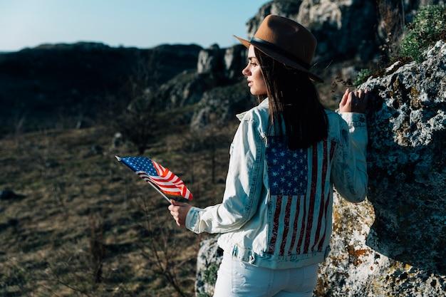 Morena en chaqueta de mezclilla con bandera americana en la naturaleza