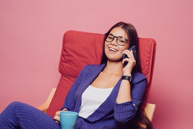 Morena confiada con expresión alegre en traje azul oscuro a rayas, sentada en una silla roja, sosteniendo una taza de café, tiene una apariencia atractiva, hablando por teléfono, sobre fondo rosa.