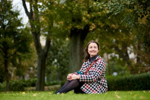Morena con una dulce sonrisa se sienta en la hierba verde en el parque mirando a lo lejos