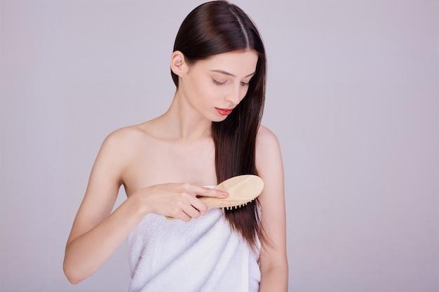 Morena envuelta en una toalla de baño blanca se peina con un peine