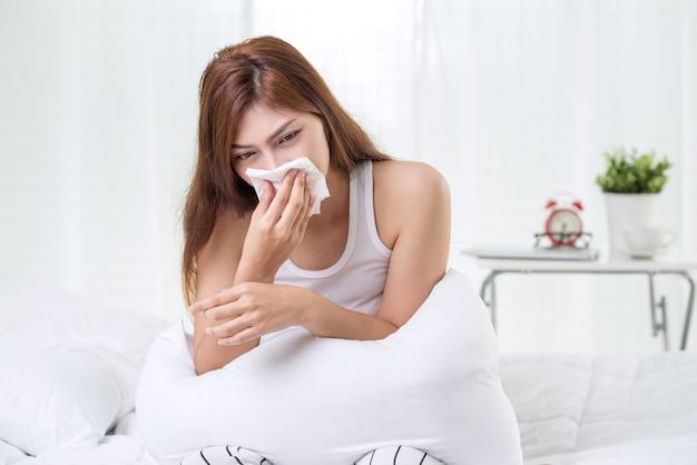 Morena estornudando en un pañuelo en la sala de estar