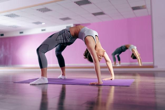 Morena en forma centrada en ropa deportiva haciendo pose de puente sobre la estera en el gimnasio.