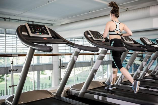 Morena en forma corriendo en cinta en el gimnasio