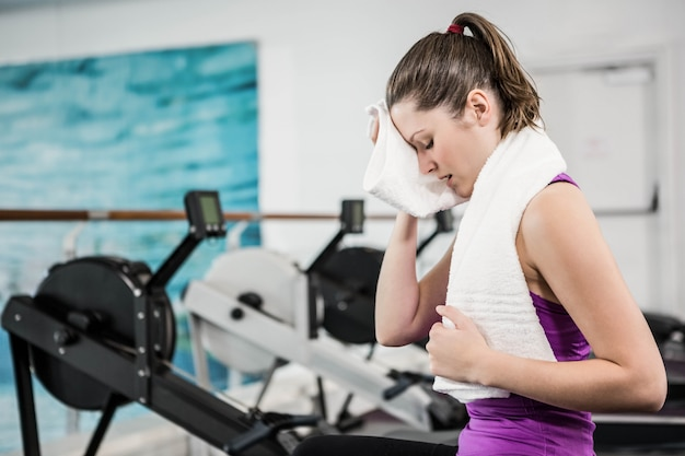 Morena en forma limpia el sudor con una toalla en el gimnasio