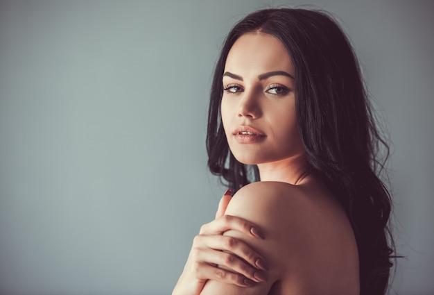 Morena con hombros desnudos mirando sensualmente a la cámara.