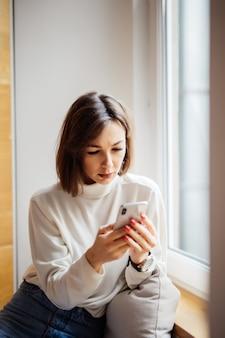 Morena interesada bonita mujer adolescente en camiseta blanca con mensajes de texto de teléfono inteligente