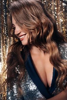 La morena de moda y lujosa en una placa base con lentejuelas y cabello sano y fuerte llegó a la fiesta de año nuevo