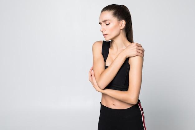 Morena molesta joven herida brazo durante el entrenamiento deportivo, toca su muñeca aislada en la pared blanca