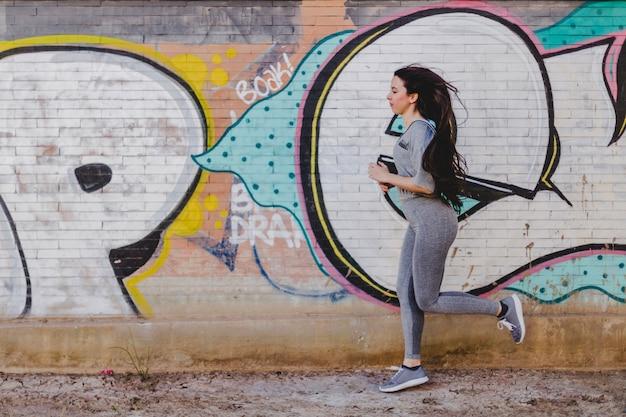 Morena mujer corriendo contra el muro de hormigón