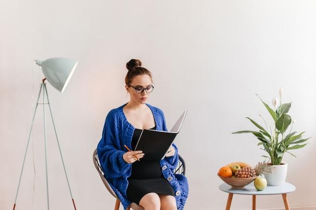 Morena mujer embarazada en anteojos lee el libro y toma notas. señora con chaqueta de punto azul oscuro y vestido negro tiene un cuaderno grande.