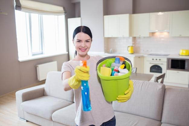 Morena de pie y posando en la cámara. ella sostiene una botella con atomizador azul y un balde con equipo de limpieza. ella sonríe y apunta a la cámara.