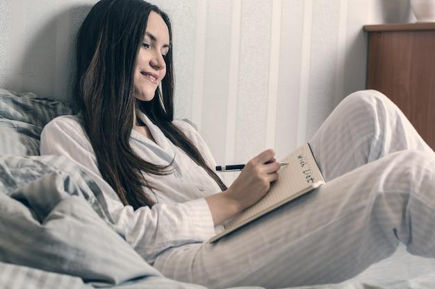 Morena en pijama azul se acuesta en la cama por la mañana y hace una lista de deseos