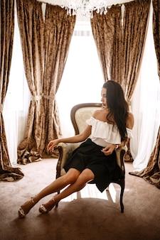 Morena seductora en interior de lujo. chica delgada rica elegante en vestido sexy con cabello brillante saludable en el apartamento del hotel villa. moda glamorosa tiro en resort de vacaciones primavera-verano