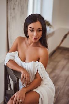 Morena sexy sentada en un vestido blanco junto a la ventana.