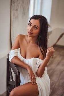Morena sexy en vestido blanco sentada junto a la ventana