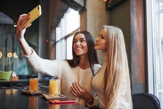 Morena sincera tiene una bonita sonrisa. jóvenes amigas toman selfie en el restaurante con dos bebidas amarillas en la mesa